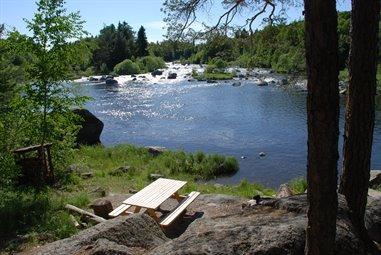 Naturmiljö med en fors med klippig strand. Bredvid forsen finns ett bänkbord.