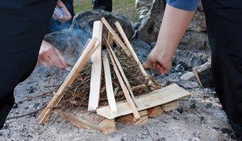 Torrt ris och vedträn staplade i en pyramid. Två händer med tändstickor nära pyramiden.