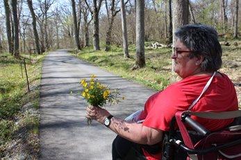 En kvinna med röd tröja sitter i en rullstol och håller i en bukett gula blommor.