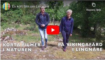 Två kvinnor går i en hage. I bakgrunden syns träd.