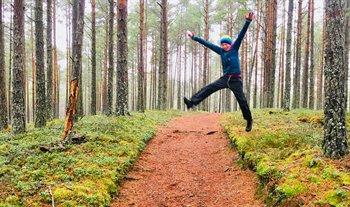 En pojke hoppar över en bred stig som går genom gles tallskog. Marken täcks av mossa och blåbärsris.