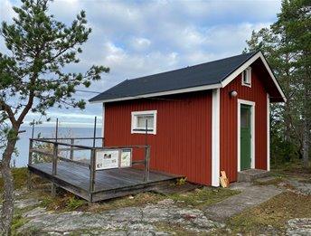 En liten röd stuga med grön dörr och en terass av trä. I bakgrunden ser man havet.